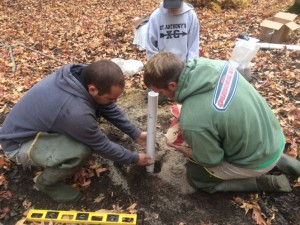 Securing the PVC pipe with sand during a well installation.