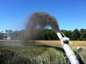 Dredge material being sprayed on marsh surface.