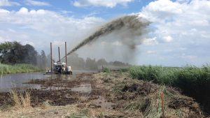 Dredge spraying mud onto marsh surface at the Prime Hook National Wildlife Refuge. Photo Credit: USFWS